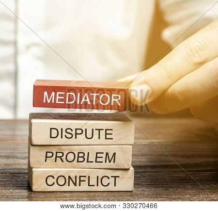 A Man Holds Wooden Blocks With The Word Mediator, Dispute, Problem, Conflict. Settlement Of Disputes