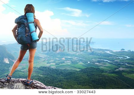 Backpacker on top of a mountain enjoying valley view