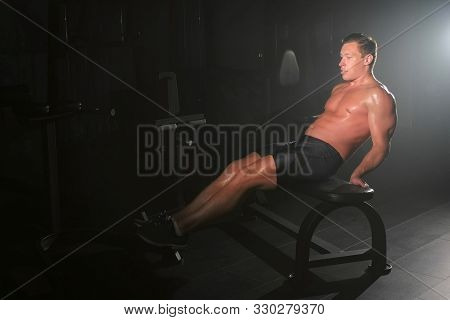 Bodybuilder young man is training his abdomen on bench, abs workout in gym, side view. White smoke in gym in dark. Sport motivation. Fit model with perfect muscular body, naked torso in shorts. poster