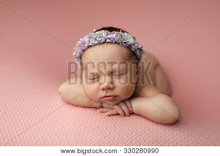 Closeup Portrait Of A Beautiful Sleeping Newborn Baby Girl On A Pink Background.