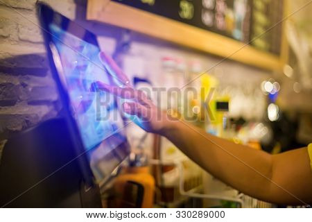 Blurry Picture Of Cashier Is Making Order On Touch Screen Of Computer In Cafe Or Store. Barista Is U