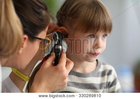 Pediatrician Examines Ear Of Sick Child In Office Of Hospital Background. Otitis Prevention Concept