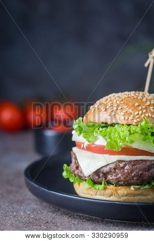 Hamburger With Beef Meat Burger And Fresh Vegetables On Dark Background. Tasty Fast Food.