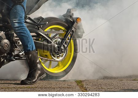 The Smoke Comes Out From Under The Wheels. Motorcycle Wheel Closeup. Smoke Due To Tire Rubbing Again