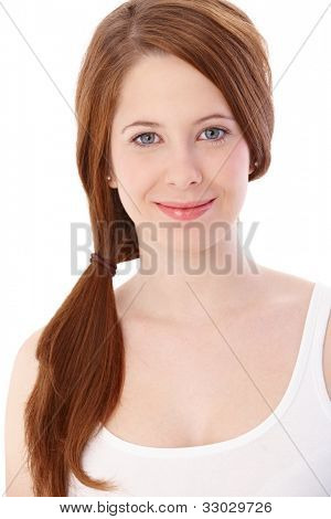 Portrait of smiling gingerish girl with long hair in pigtail.