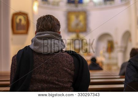 Man In Coat From The Back Close Up In Catholic Church. Bokeh Effect With Blur Background. Copy Space