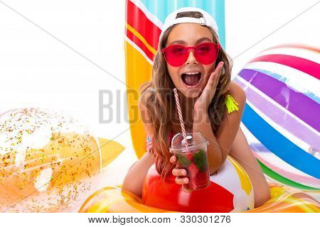 Close-up Smiling Girl On A White Background, The Child Holds Non-alcoholic Cocktails In His Hands An