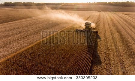 Aerial Image Of Combine Harvesting Soybeans At Sunset In A Field In The Midwest United States.