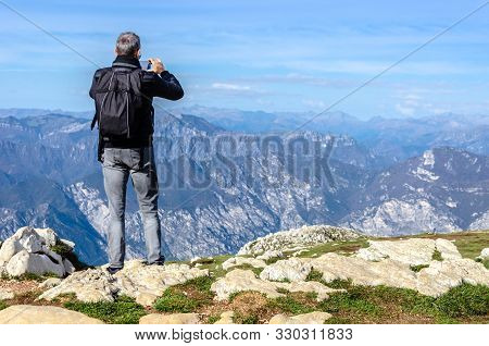 Man Takng Picture Of The Scenery O The Top Of A Mountain