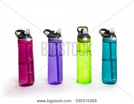 A row of colorful water bottles filled with water. Isolated on a white background.
