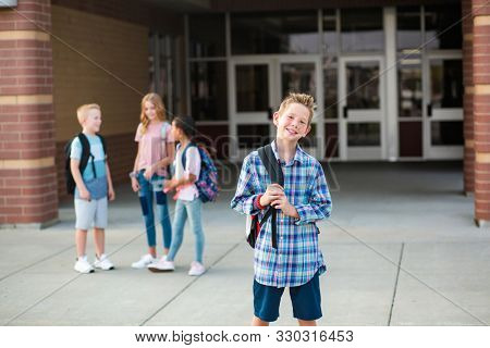 Handsome pre-adolescent teen boy student hanging out with friends after school. Selective focus on the smiling boy student standing outside the school building with friends in the background