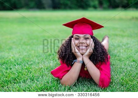 Portrait of a beautiful multiethnic woman in her graduation cap and gown. Smiling and cheerful as she poses lying in the grass