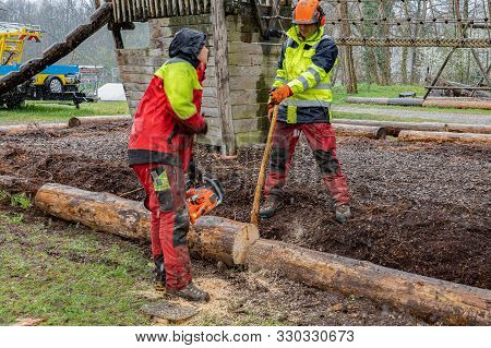 Young Loggers Working On A Playground With Tree House, Cutting Tree Trunk With Chain Saws In Rainy D