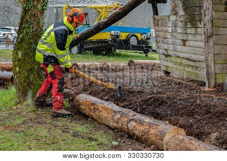Young Loggers Working With An Ax On A Playground, After Cutting Tree Trunk With Chain Saws In Rainy