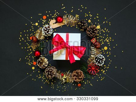 Chirstmas Wreath Decoration And Gift Box. Flat Lay, Top View. Black Background. Golden Confetti. Cop