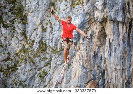 Highline In The Mountains. A Man Goes On A Stretched Sling. Highliner Is On The Line. A Tightrope Wa