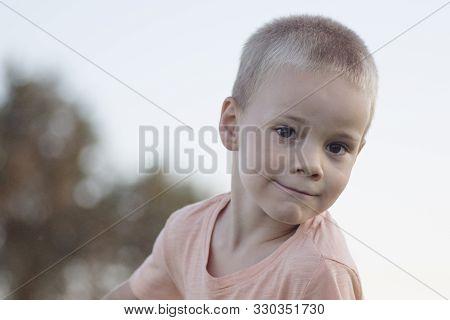 Child Portrait Of Blonde Cute Little Boy Outdoors.
