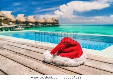 Christmas Santa Claus luxury vacation gift hotel holidays - hat by the infinity swim pool of high end resort for tropical sun vacation getaway during winter holiday. Overwater bungalows villas.