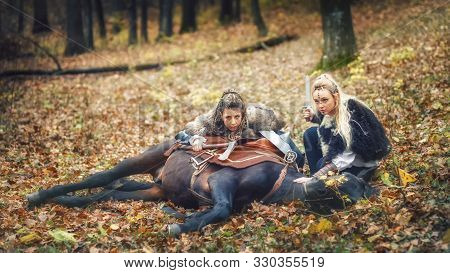 Outdoor Portrait Of Northern Viking Warrior Women With Braided Hair And Painted Faces With Their Hor