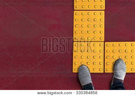 Shoes On Rough Yellow Dot Tactile Paving For Blind Handicap On Tiles Pathway In Japan, Walkway For B