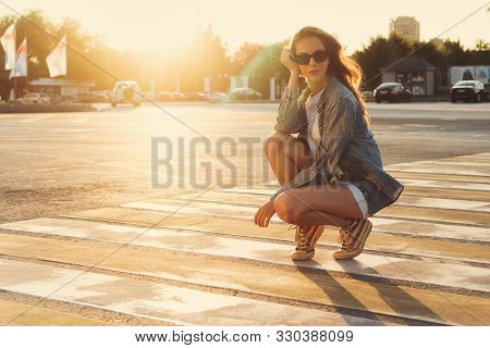 Lovely Teenager Girl Posing At The Crosswalk In The Sunset. Happy Summer, Vacation, Travel. Summerti