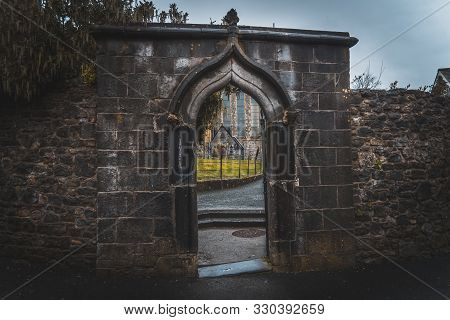 Kilkenny, Ireland, December 23, 2018: Spooky Old Stone And Very Wet Entrance Gate Of A Graveyard Wit
