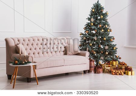 Beautiful Beige Sofa, Christmas Tree With Decorations And Gifts, A Table With Candles. Cozy Christma
