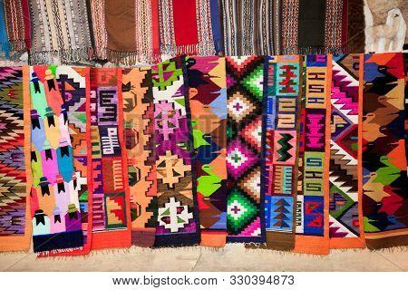 Machu Picchu Pueblo,  Peru - Jan 7, 2019: Peruvian traditional colourful native handicraft textile fabric at market in Machu Picchu, Cusco ,  Peru.
