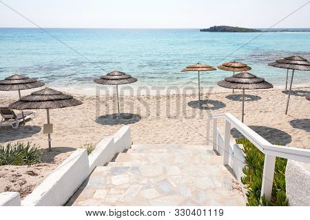Reed Beach Umbrellas, Sunshades Against Blue Sky On The Beach. Bamboo Parasols, Straw Umbrellas On O