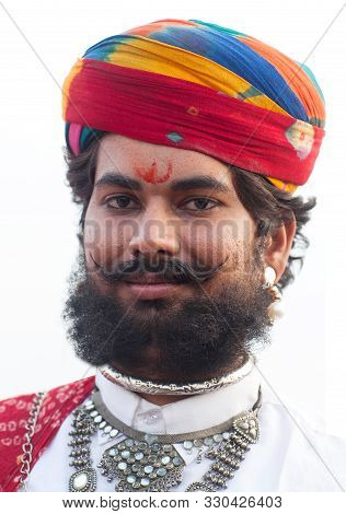 Bikaner, India - January 12, 2019: Indian Smiling Rajasthani Man With Long Mustache Poses For A Phot