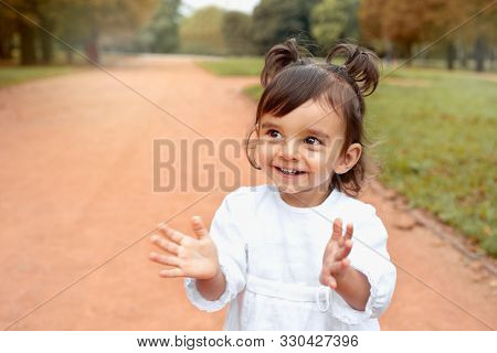 Little Happy Smilling Baby Girl Clapping Hands In The Park