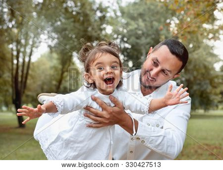 Happy Little Girl Having Fun With Her Father In The Park