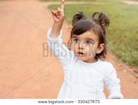 Little Amazed Baby Girl Pointing Finger Up In The Park