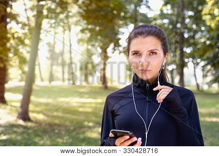 Portrait Of Young Sporty Brunette Woman Running With Headphones In The Park Outdoor