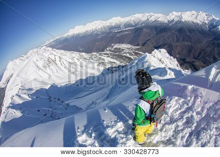 Freerider Snowboarder In Helmet With A Backpack Stands On The Slope Of The Mountains Of The Caucasus