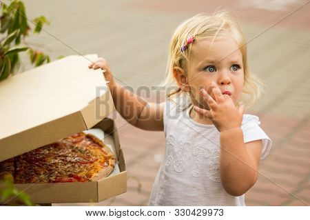 A Little Girl Opens A Box Of Pizza. Licks His Finger, It Is Very Tasty. Pizza Delivery.