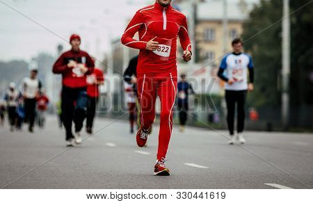 Male Runner In Red Tracksuit Run Marathon Ahead Of Group Runners