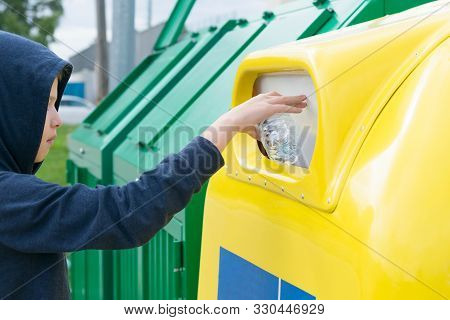A Boy In A Blue Sweater With A Hood Throws An Empty Bottle Into The Trash Can