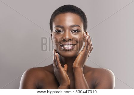 Beautiful Black Woman With Short Hair Touching Her Smooth Cheeks, Applying Cream Or Lotion On Face A