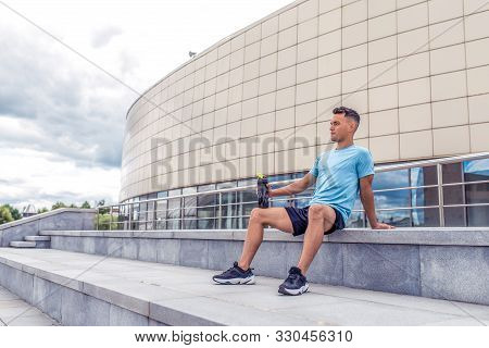 Sports Man Resting After Hard Workout, Shaker With Protein And Water, A Daytime Workout In City, Act