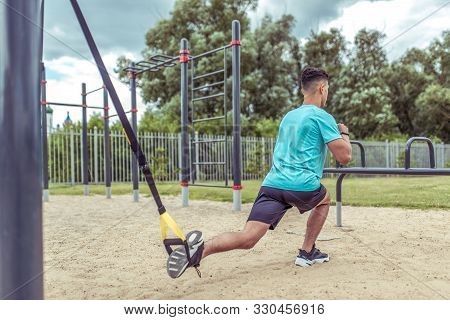 Athletic Man Exercises With Straps Loops Trx, Lunges Workout Leg Muscles, Workout In Summer In City,