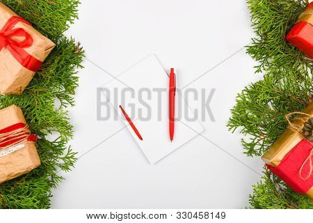 poster of notebook with pen on christmas background. Empty white notebook and pen on white Christmas background of fir branches, cones, gifts. Letter To Santa Claus, mock up. Empty white notebook and pen on a white