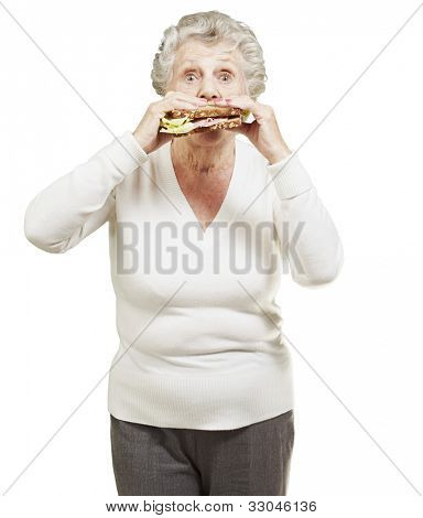 senior woman eating a healthy sandwich against a white background