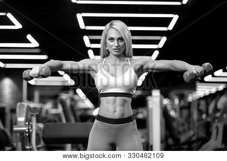Sexy Fitness Blonde Woman Is Doing Side Raise With Dumbbells In The Gym Bw