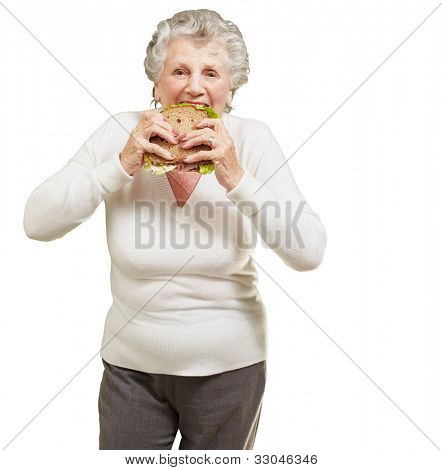 portrait of a senior woman eating a vegetal sandwich over a white background