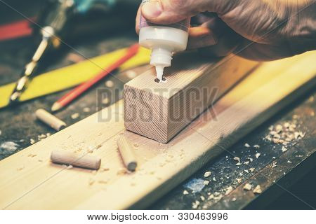 joinery - joiner put the glue into a drilled hole for wooden dowel joint poster