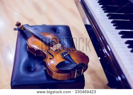 Violin And Piano On Wooden Background.