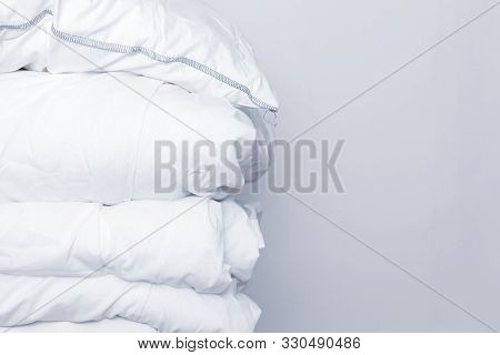 Pile Of White Bedding Items, Pillows And A Blanket On White Background With Copy Space.