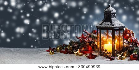 Burning candles , lantern and christmas decoration on magic bokeh lights background