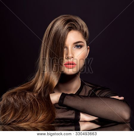 Woman with beauty long brown hair. Fashion model with long straight hair. Fashion model with a smokey makeup. Pretty woman with orange color lipstick on lips.
